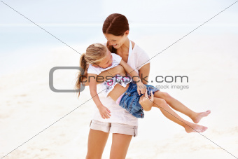 Pretty young mother carrying her daughter on the sand