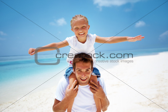 Cute young girl on her fathers shoulders on the beach