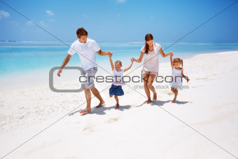 Playful young family together running at the seaside
