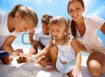 Cute young family playing together while on the beach