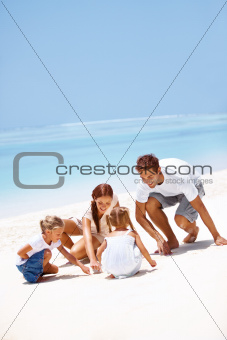 Cute young family playing in the sand together