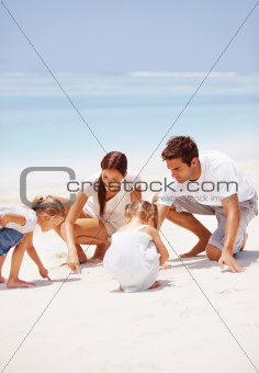 Tanned young family playing in the sand at the beach