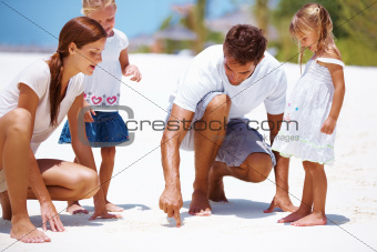 Young father playing in the sand with his family watching