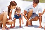 Cute little girl pointing at something on the sand and showing her parents