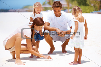 Pretty young mother playing with her family at the beach