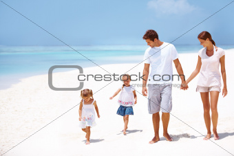 Cute young family walking together on the beach