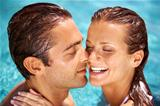 Beautiful woman laughing with her partner while swimming together