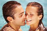 Pretty woman laughing while swimming with her partner