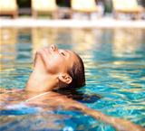 Sensual young woman relaxing in a swimming pool