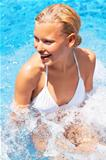 Portrait of of beautiful young woman enjoying cool water in pool