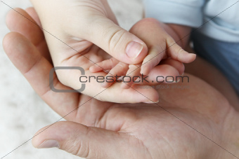 Hands of mother, father and baby