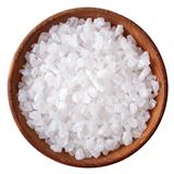 Wooden bowl full of sea salt over white