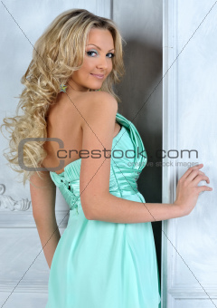 Beautiful blonde woman in blue dress at the opening door.