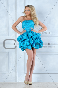 Beautiful blonde girl in short blue evening dress.