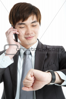 asian businessman checking time while talking on mobile phone