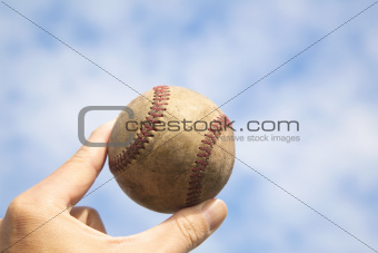 hand holding old baseball with cloud background