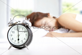 The clock and Young beautiful woman sleeping
