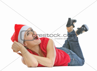 Happy woman in Christmas hat laying on floor and looking on copy space