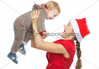 Mother in Santa's hat playing with baby