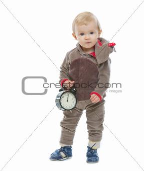 Baby in Santa's deer costume holding alarm clock