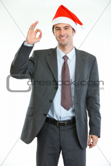 Smiling businessman in Santa's hat showing ok gesture