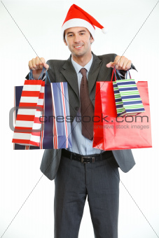 Smiling businessman in Santa's hat showing shopping bags