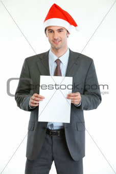 Smiling businessman in Santa's hat showing blank paper