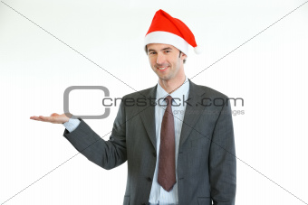 Smiling businessman in Santa's hat presenting something on empty palm