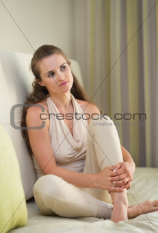 Portrait of thoughtful young woman sitting on divan