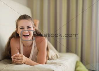 Portrait of laughing young woman laying on divan
