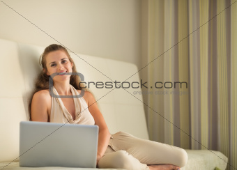 Portrait of happy young woman sitting on couch with laptop