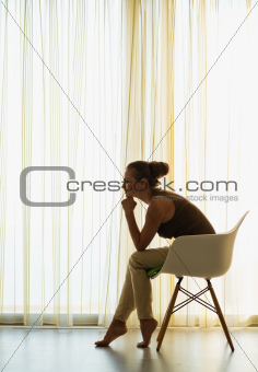 Woman sitting near window in thoughtful pose and looking on copy space