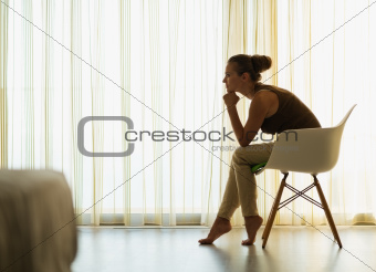 Female sitting near window in thoughtful pose and looking on copy space
