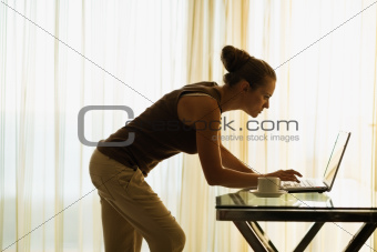 Young woman using laptop leaning against table
