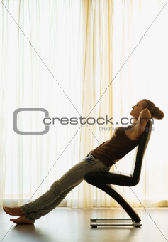 Young woman relaxing on modern chair near window