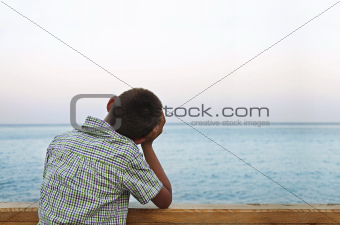 boy looking at sea in the sunset