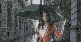 beautiful woman with umbrella in town under rain