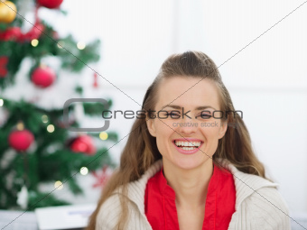 Portrait of happy young woman near Christmas tree