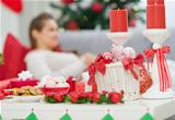 Closeup on table with Christmas decorations and female laying on couch in background