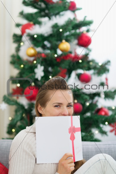 Female hiding behind Christmas postcard