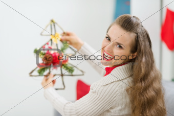 Smiling woman holding Christmas decoration tree