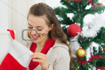 Smiling woman looking into Christmas socks