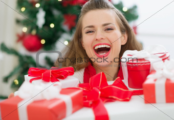 Happy woman holding stack of Christmas present boxes