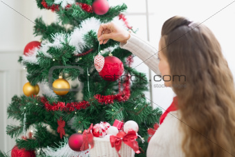 Woman decorating Christmas tree. Rear view
