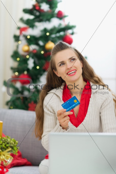Woman with credit card thinking about Christmas presents