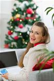 Happy young woman making online Christmas purchases