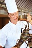 Male cook with a lobster in kitchen