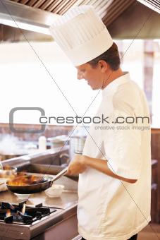 Young chef cooking food in restaurant
