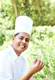 Happy young chef with basil leaves in garden