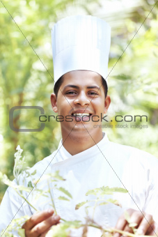 Portrait of handsome young cook in garden